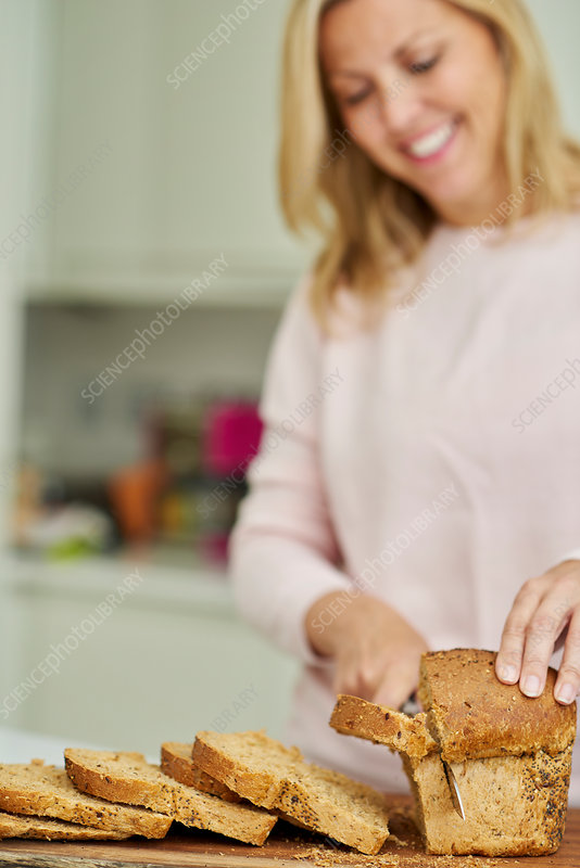 A woman slicing a loaf of brown bread