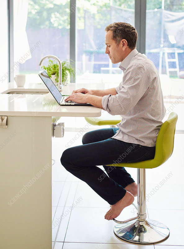 A man seated on a kitchen chair using a laptop computer