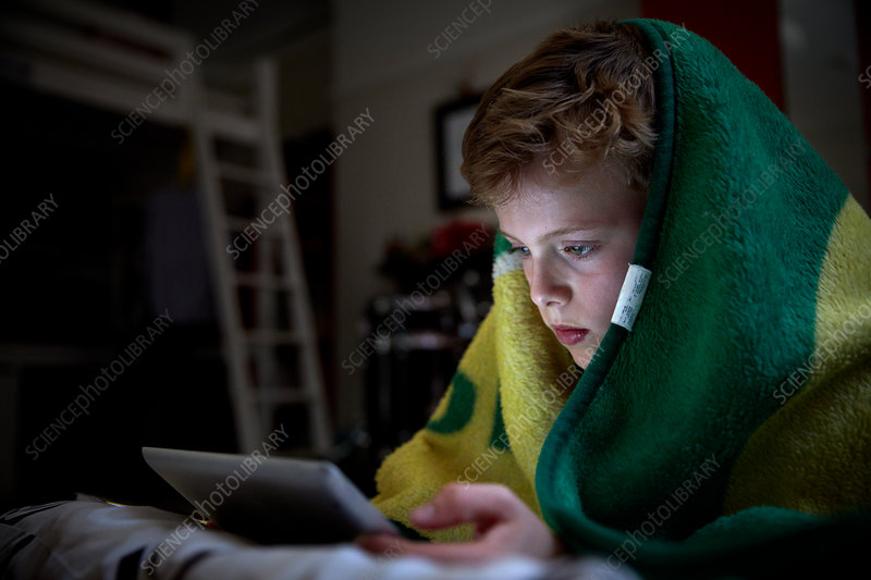 A boy with a blanket over his head lying down using a tablet
