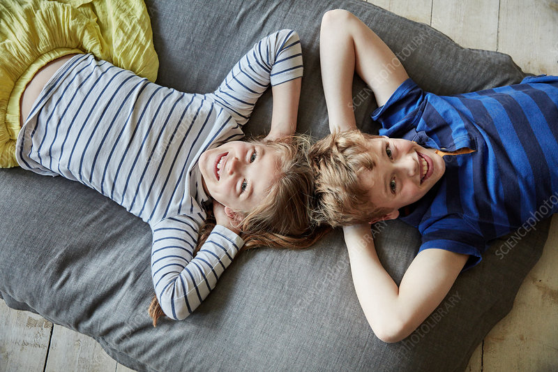 A boy and girl lying on the sofa, overhead view