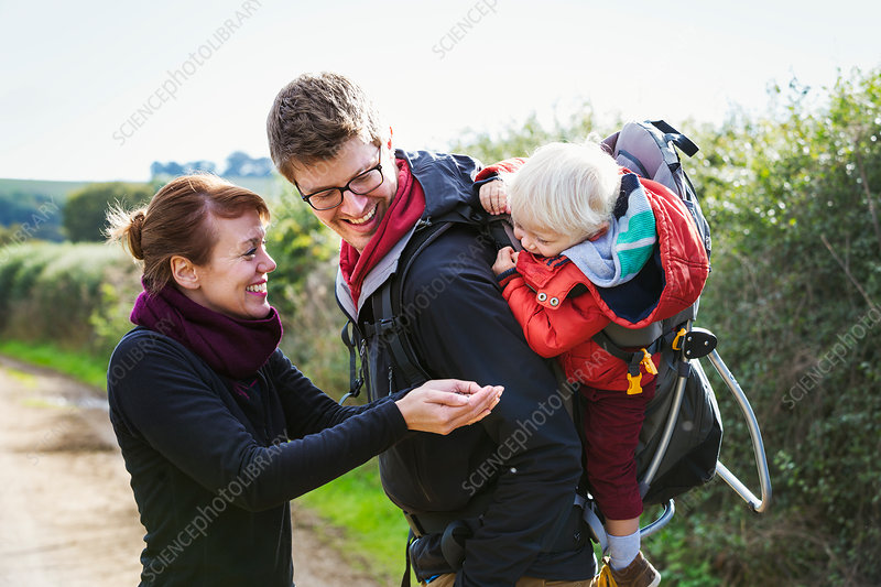 Parents and a child on a country walk, a boy in a backpack