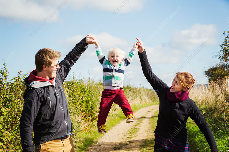 Parents holding a small boy's hands and lifting him up