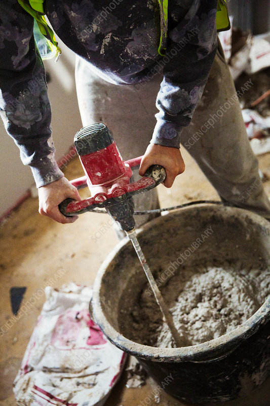 A builder mixing plaster in a bucket