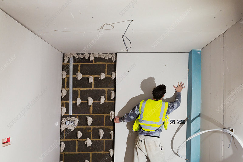 A building worker fitting plasterboard on a block wall