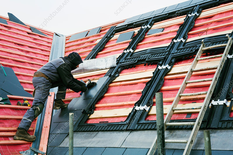 A roofer replacing the tiles on a house roof