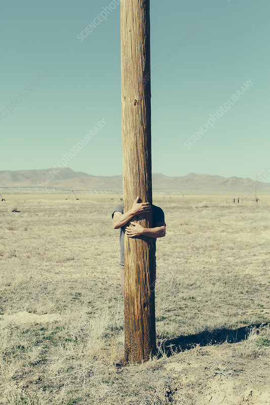 Man with his arms around a wooden utilities pole