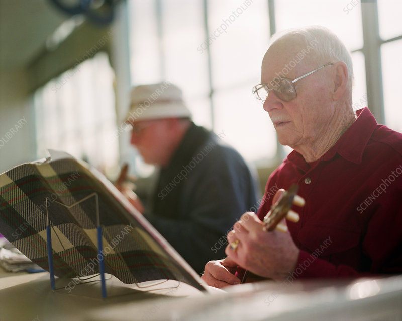 Two elderly men playing ukulele instruments