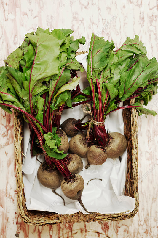 Beets in a basket on a wooden surface