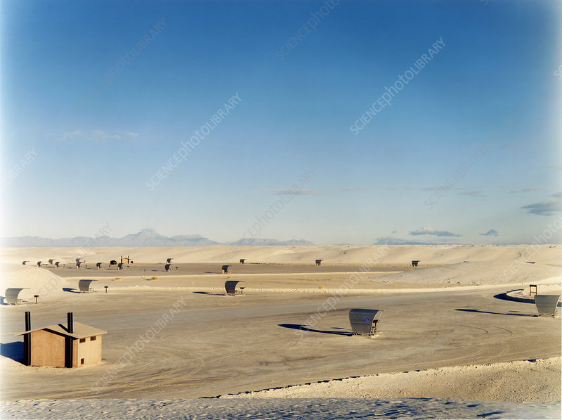 An open space, a desert landscape with sun shelters