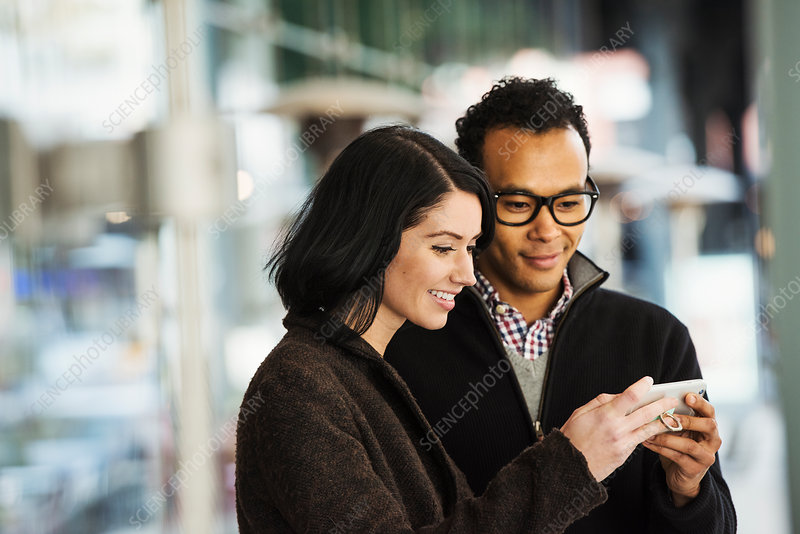 A young man and woman holding a cell phone together