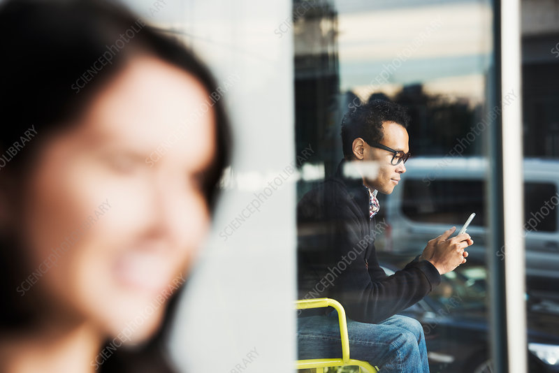 A seated woman seen in a window looking at a cell phone