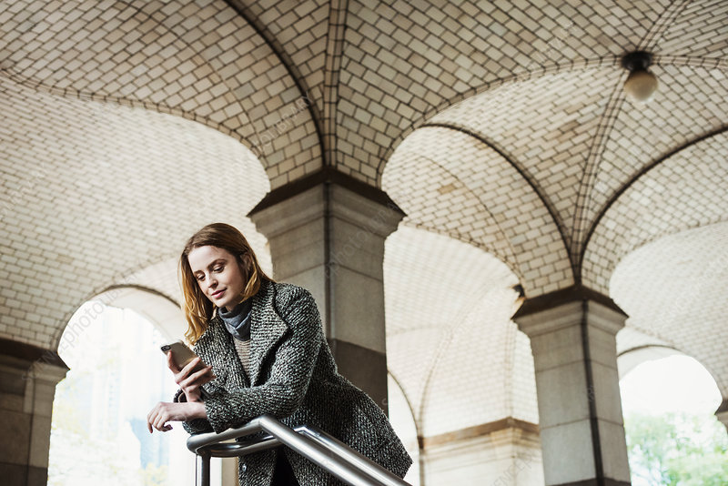 A woman looking at her smart phone, under an archway