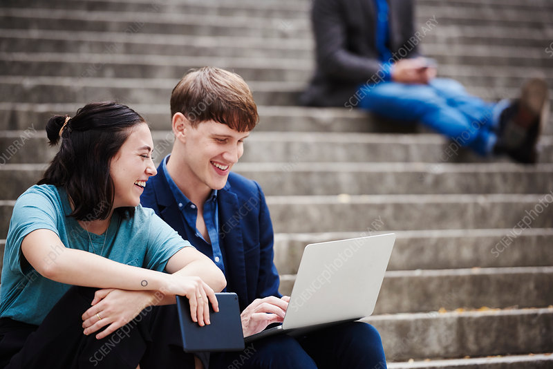 A young woman and a young man outdoors looking at a laptop