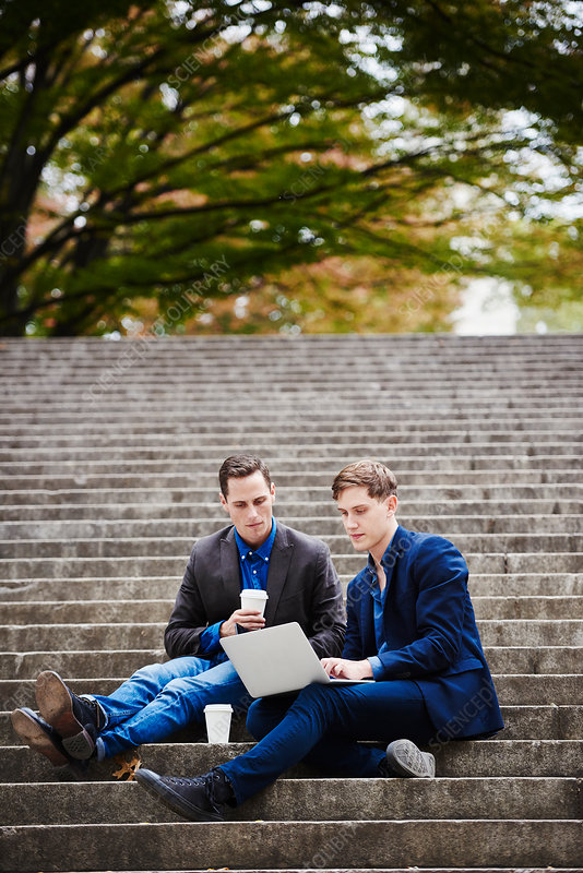 Two young men sitting looking at a laptop together