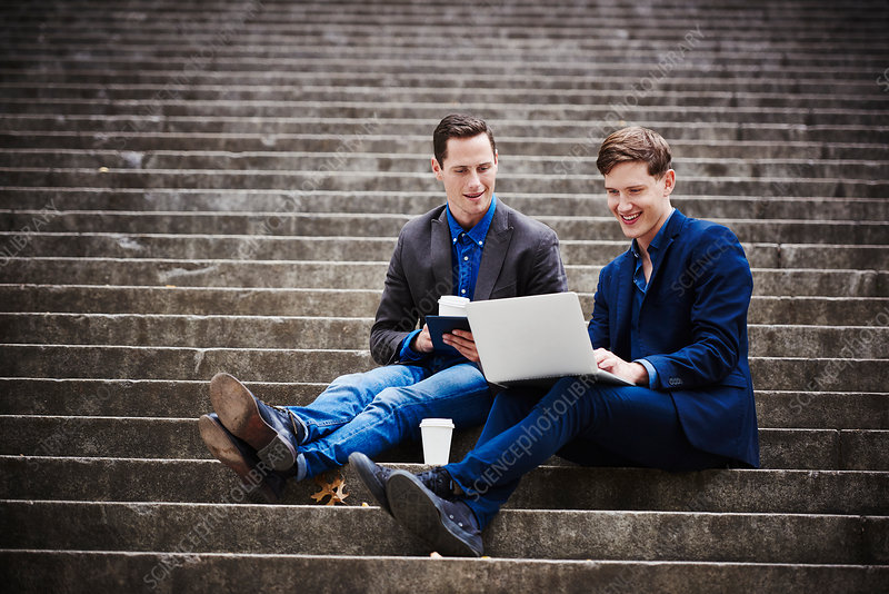 Two young men outdoors looking at a laptop together