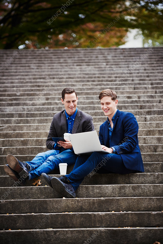 Two young men sitting outdoors looking at a laptop together
