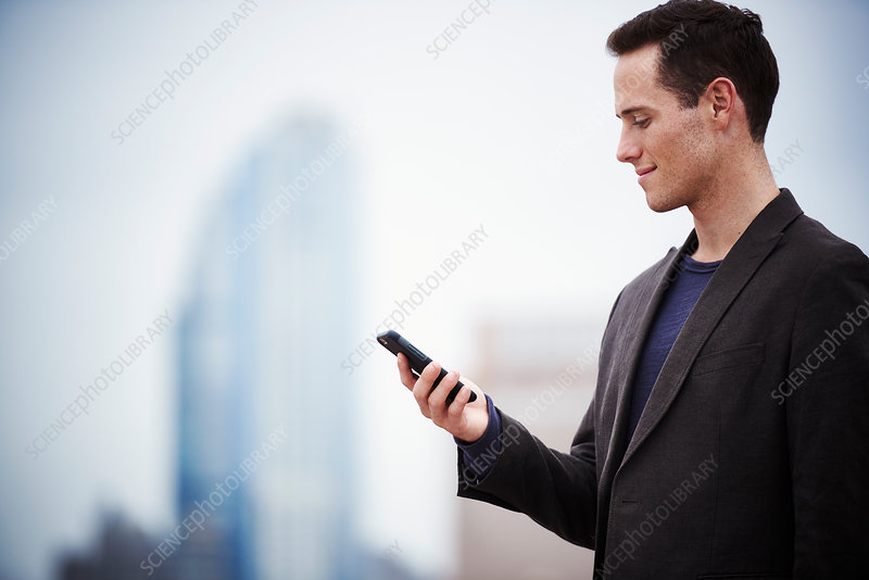 A young man on a rooftop looking down at a cell phone