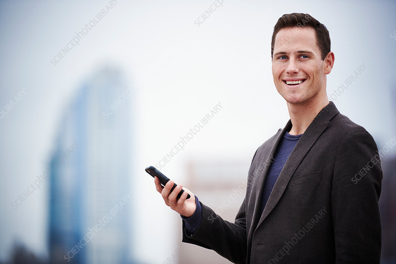 A young man standing on a rooftop holding a cell phone