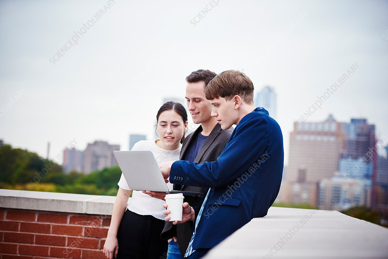 A woman and two young men on a rooftop looking at a laptop