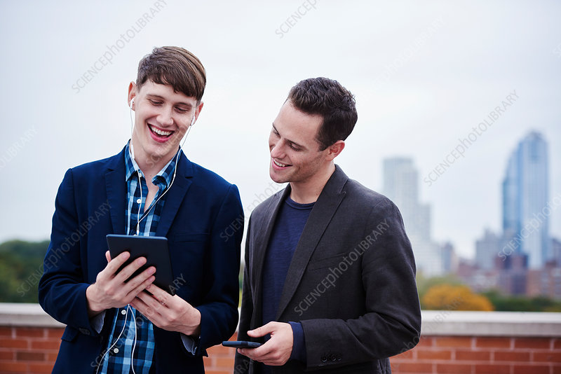 Two young men standing looking at a tablet together