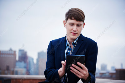 A young man standing on a rooftop looking down at a tablet