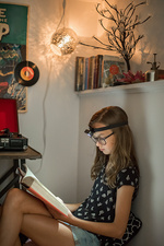 A girl reading a book in a quiet corner using a head torch