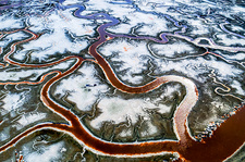 Aerial view of meandering water channels and salt pans