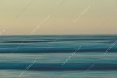 Ocean waves and a view to the horizon over sea at dusk