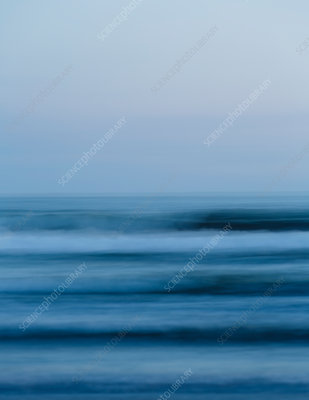 Ocean waves and the view over the sea at dusk