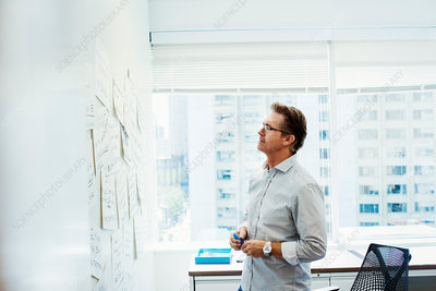 A man standing in an office looking at a whiteboard