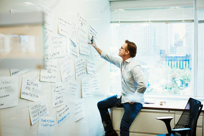 A man leaning on a desk looking at a whiteboard
