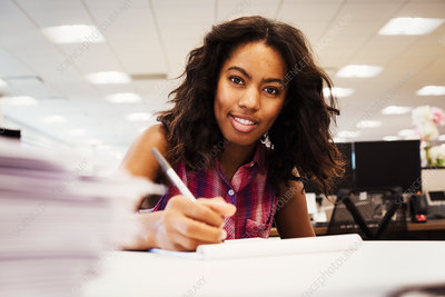 A woman sitting at a desk in an office, holding a pen
