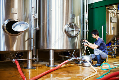 Man working in a brewery, kneeling beside a metal beer tank