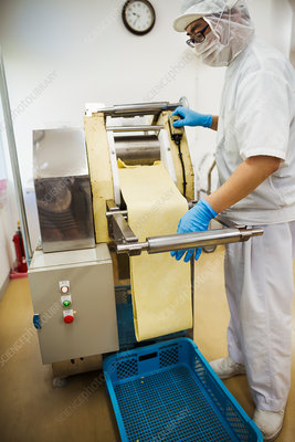 Worker in factory rolling out noodle dough in thin sheets
