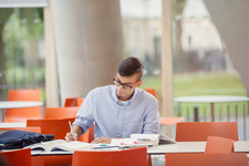 Male college student studying at table