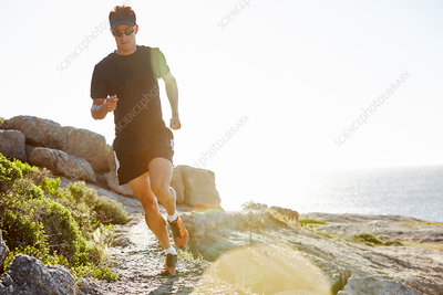 Male triathlete running on rocky trail along ocean