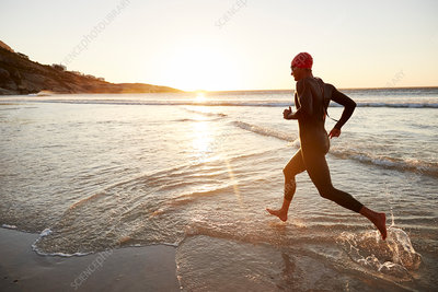 Male triathlete swimmer running into ocean surf