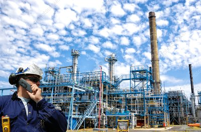 Industrial worker on oil and gas refinery using cell phone