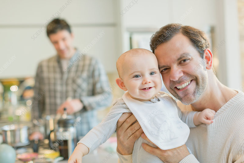 Portrait smiling gay father holding baby son