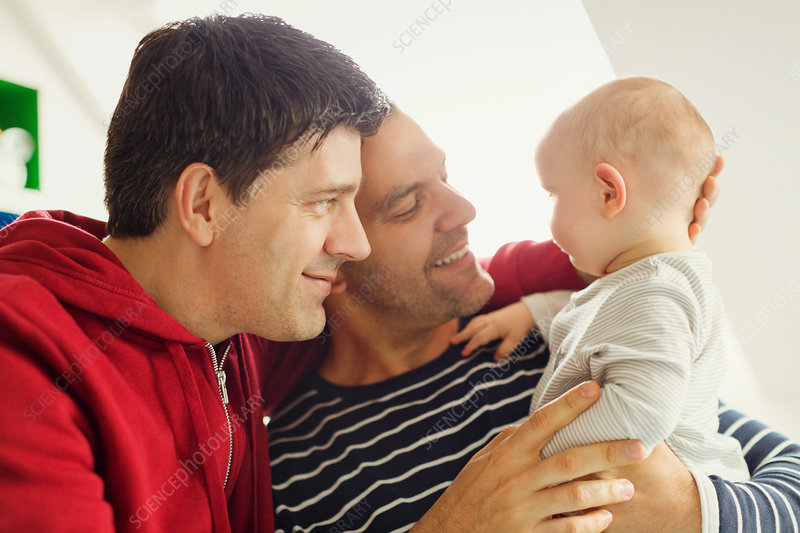 Affectionate male gay parents cuddling baby son