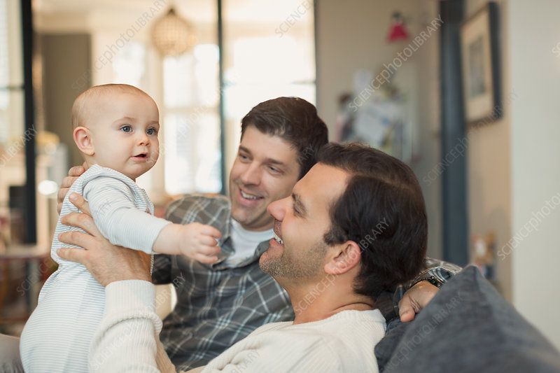 Male gay parents holding baby son on sofa