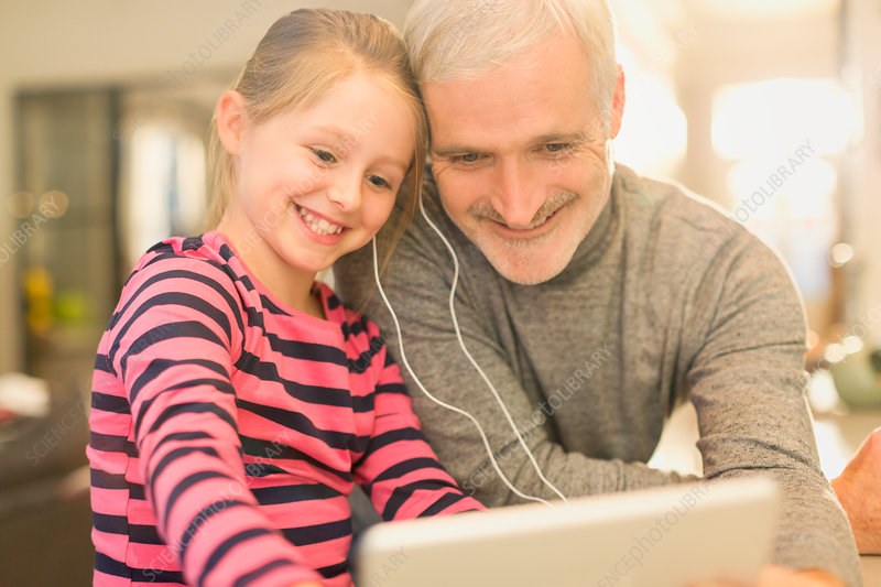 Smiling father and daughter sharing headphones