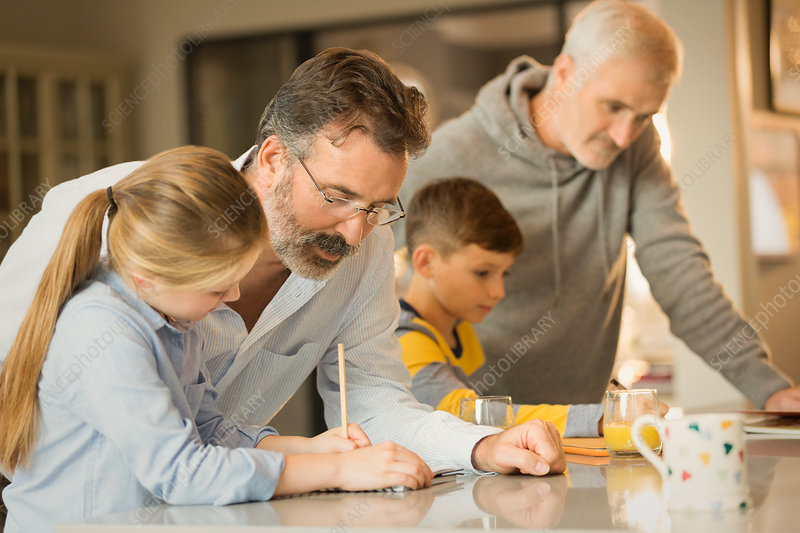 Male gay parents helping children doing homework