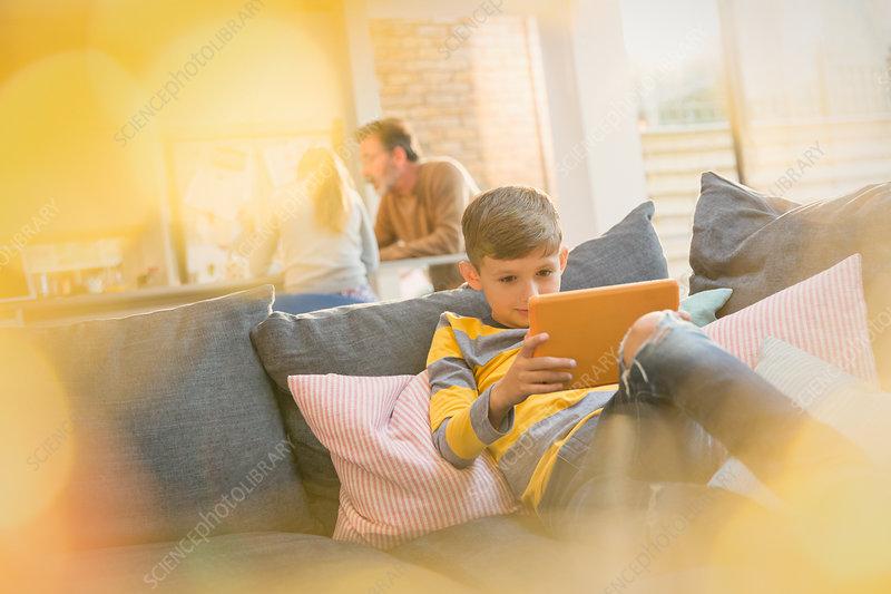 Boy using tablet on sofa