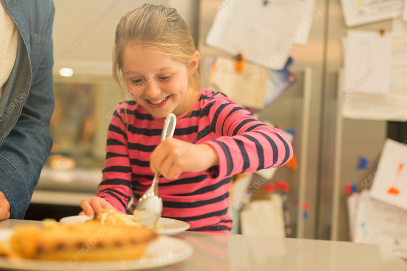 Smiling, eager girl serving pie