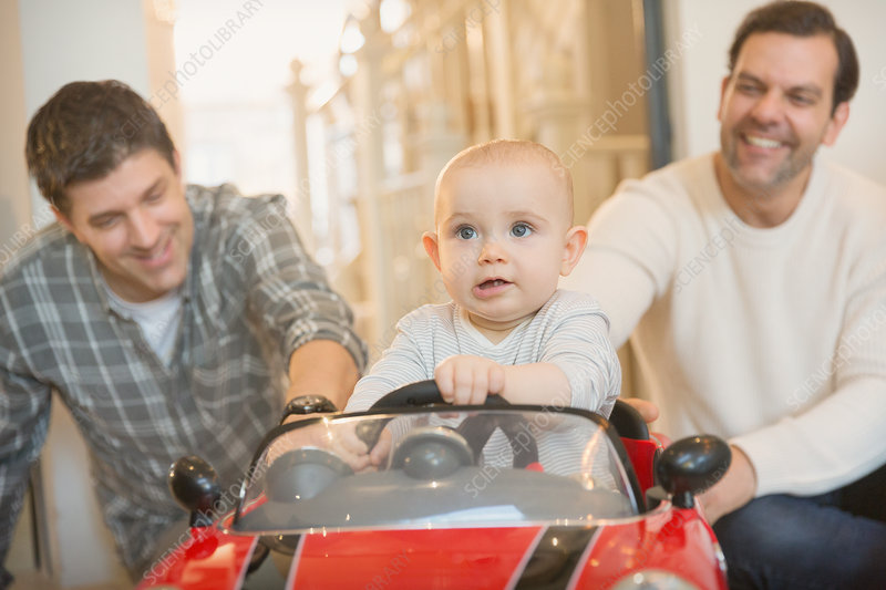 Male gay parents pushing baby son in toy car