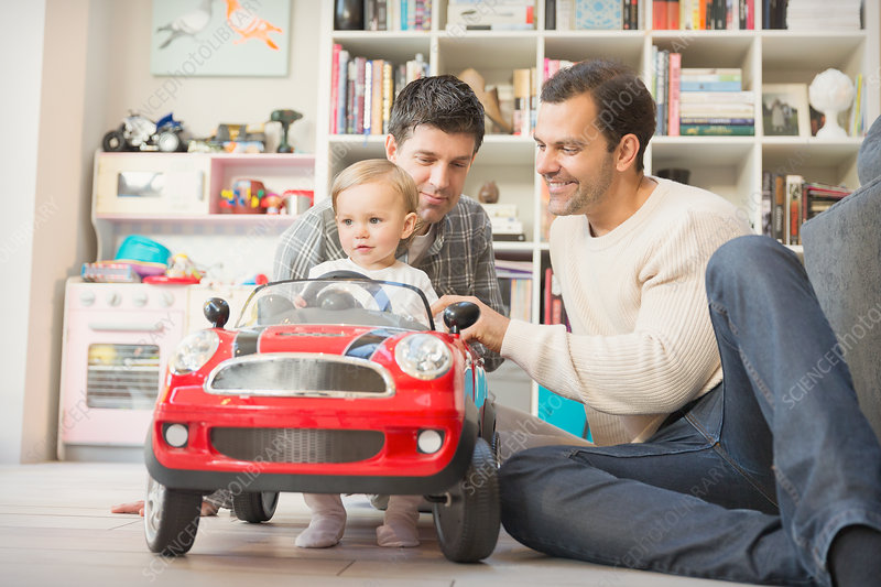 Male gay parents and baby son playing with toy car