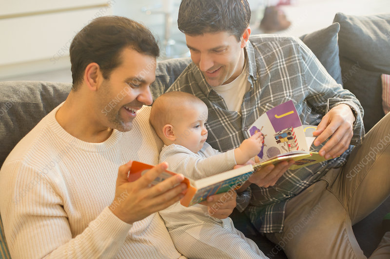 Male gay parents reading book to baby son on sofa