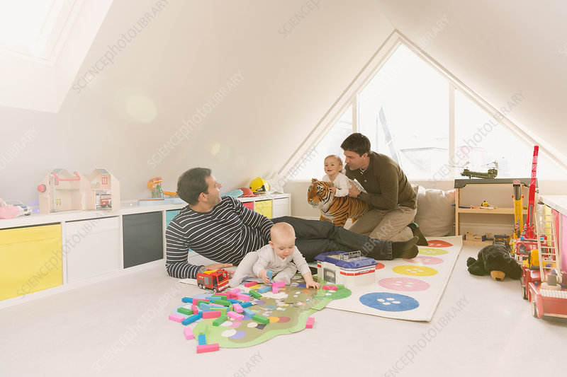 Male gay parents playing with baby sons