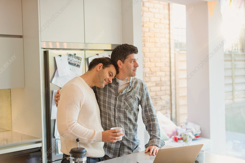 Affectionate male gay couple with coffee